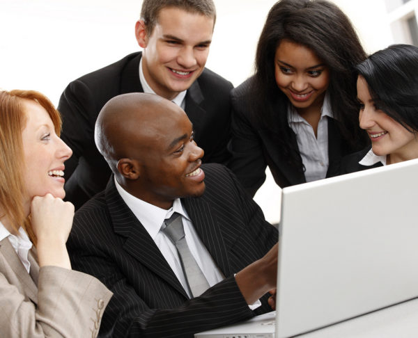 multiracial business team looking at a laptop